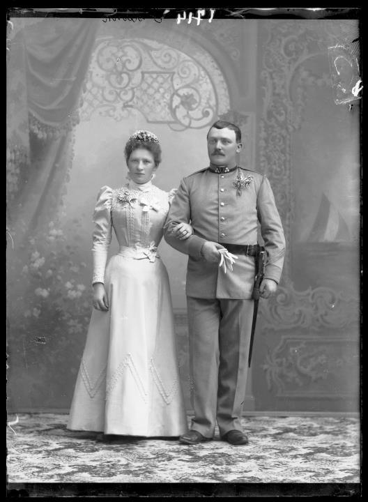Studioaufnahme. Gruppenporträt: ein Soldat in Uniform und eine Frau, beide mit angesteckten Blumenn