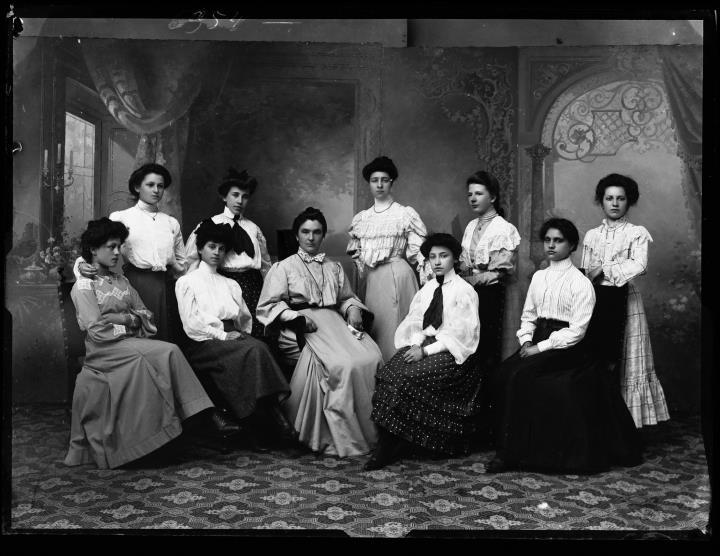 Studioaufnahme. Gruppenporträt von zehn Frauen im Fotostudio Waldmüller