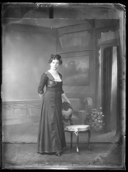 Studioaufnahme. Porträt einer stehenden Frau neben einem Stuhl