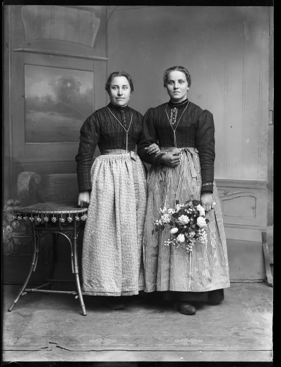 Studioaufnahme. Gruppenporträt von zwei stehenden Frauen in Tracht. Eine hält einen Blumenstrauß in der Hand